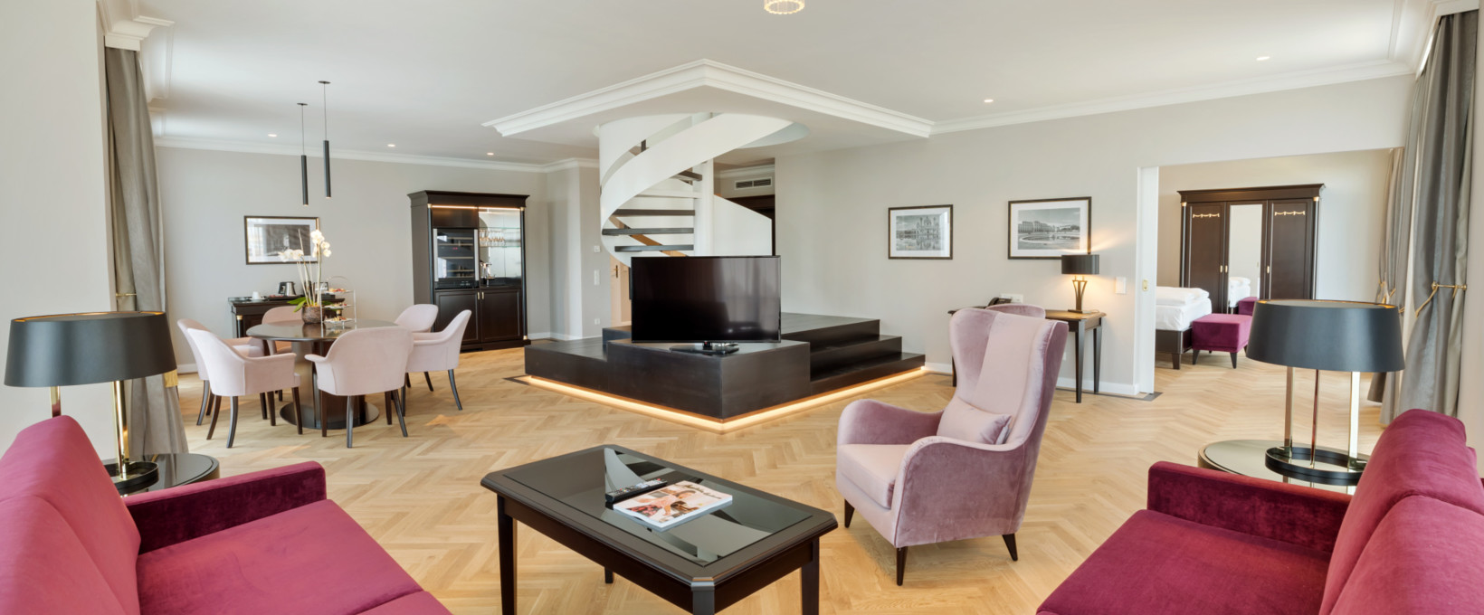 Kaiser Suite living room with seating area, TV and winding stairs | Parkhotel Schönbrunn in Vienna