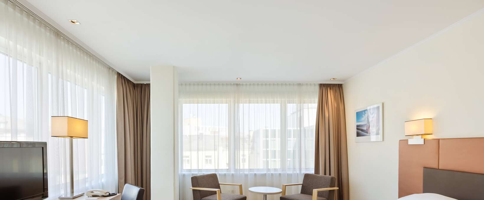 Executive Deluxe Room with kingsize bed, seating area and TV | Hotel Schillerpark in Linz